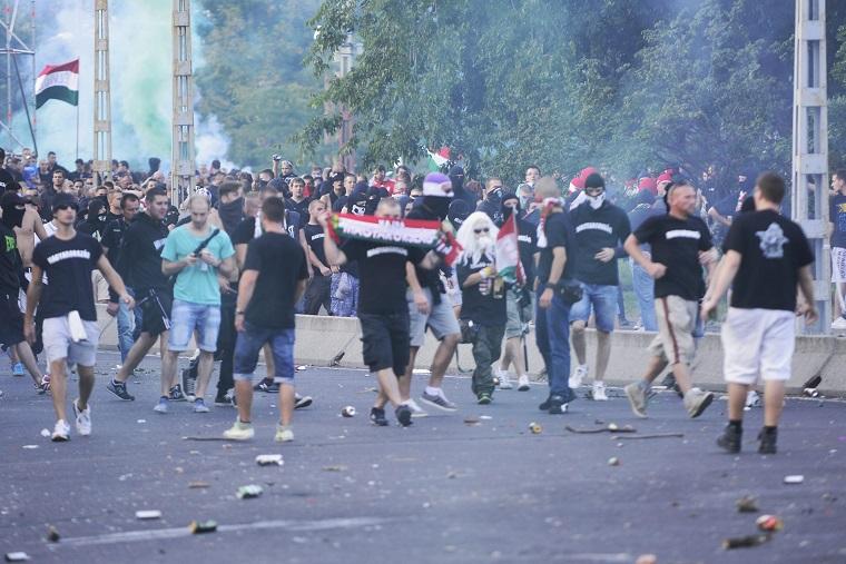 Szurkolók dobálják a rendőröket a magyar-román előtt. Fotó: MTI / Marjai János