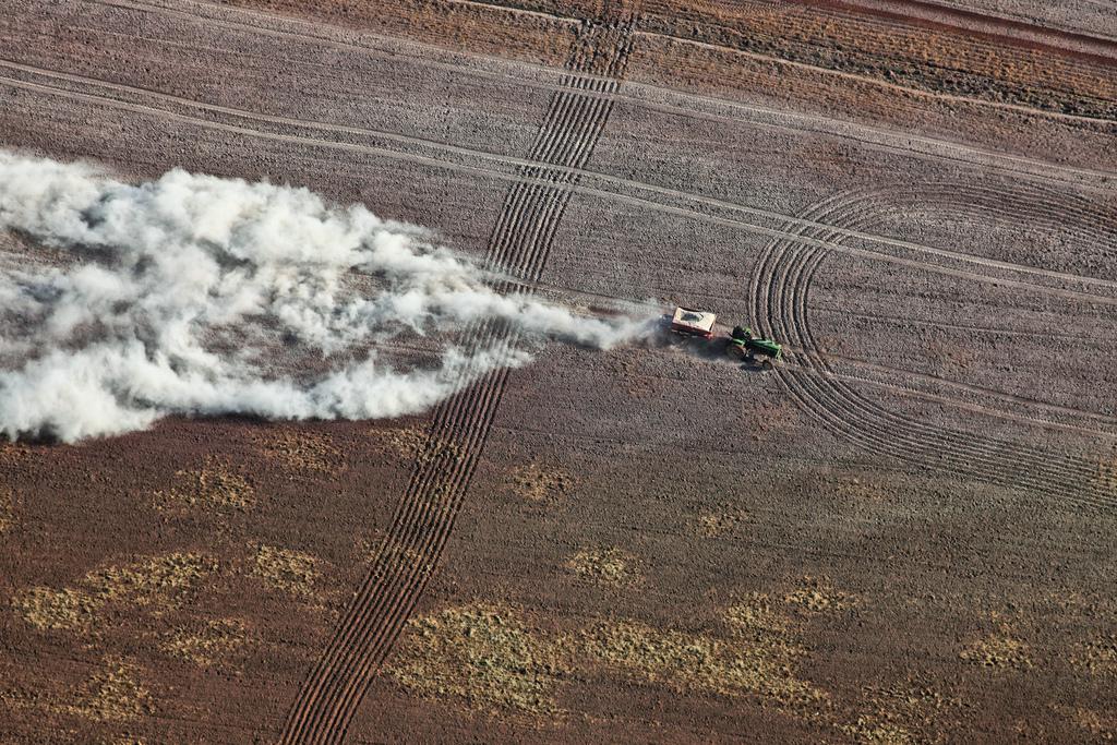 Luftaufnahme von einem Landwirt beim Ausbringen von Kalk auf seine Felder